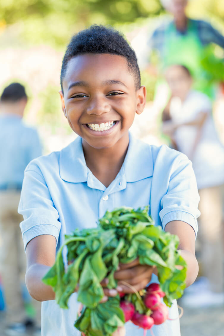 Young boy holding fresh vegetables smiling